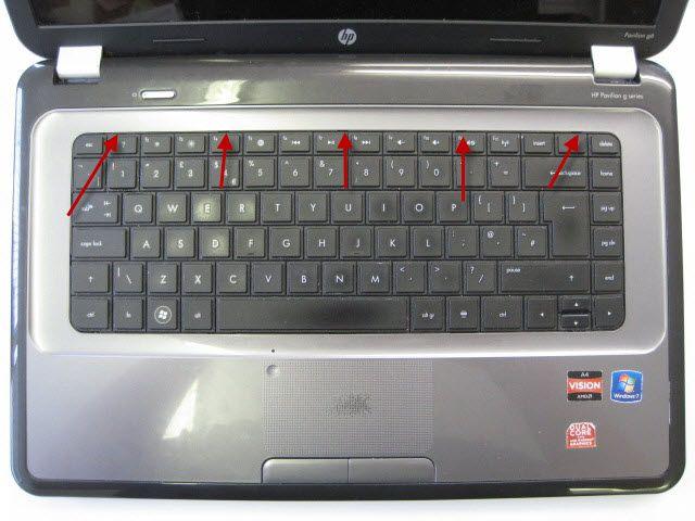 Включите ноутбук и снимите клавиатуру.  Стрелки указывают на небольшие клипы, которые держат в клавиатуру, которая нужна отодвигая
